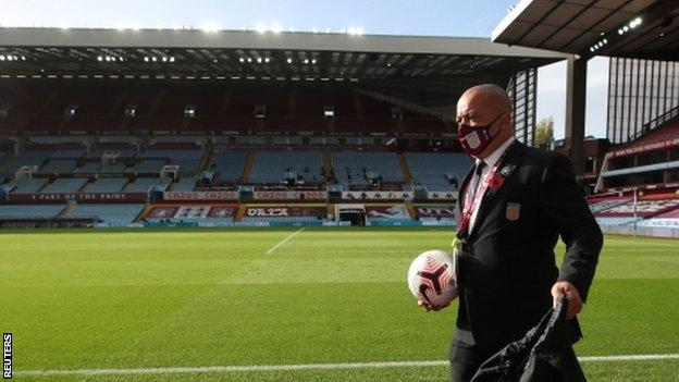 A member of Aston Villa's staff wearing a face mask before a game at Villa Park